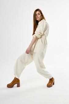 Vrouw in bruine laarzen witte jumpsuit mode studio lichte achtergrond
