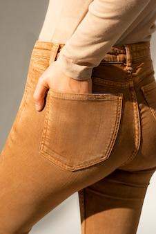 Vrouw in bruine spijkerbroek met hand in zak