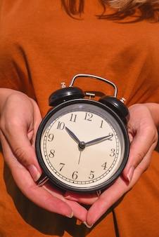 Vrouw in bruine t-shirt wekker in de hand houden.