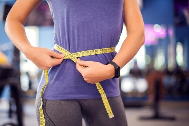 Vrouw in bue shirt taille meten met meter in de sportschool. mensen, fitness en gezondheidsconcept