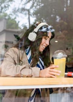 Vrouw in café met verse limonade en koptelefoon