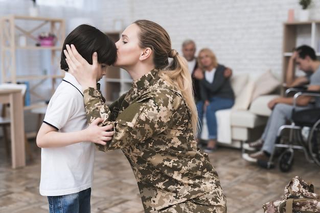 Vrouw in camouflage uniform kust haar zoon.