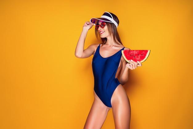 Vrouw in cap en badmode bedrijf plak van watermeloen