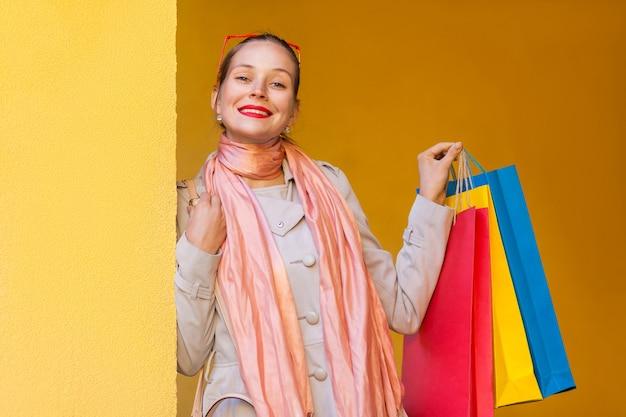 Vrouw in casual kleding met boodschappentassen die naar de camera kijkt met een glimlach