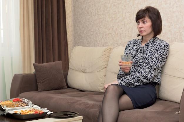 Vrouw in casual kleding met glas wijn om thuis te zitten.