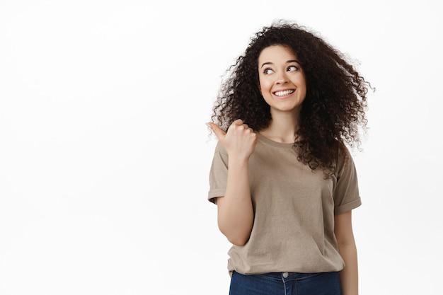 Vrouw in casual outfit wijzende vinger naar links, opzij kijkend naar kopieerruimte met een gelukkige witte glimlach die op wit staat