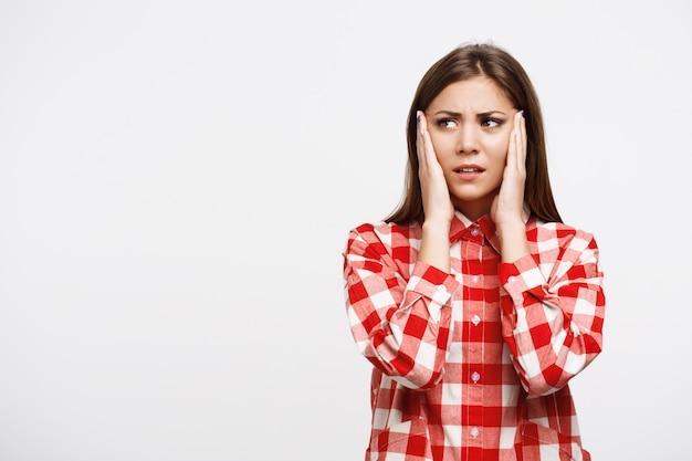 Vrouw in check shirt houden handen op het hoofd met hoofdpijn
