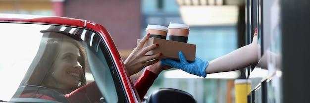 Vrouw in converteerbare auto pikt thee en koffie op