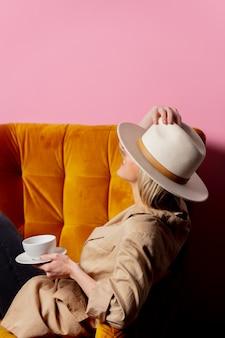 Vrouw in cowboyhoed zitten in een vintage fauteuil met kop