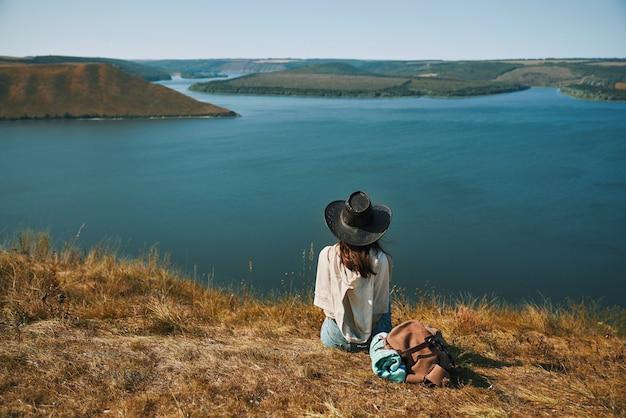 Vrouw in cowboyhoed zittend op de bergtop in de buurt van dnjestr