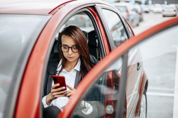 Vrouw in de auto achter het stuur kijkt naar de notificatietelefoon en leest het bericht.