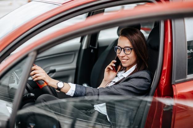 Vrouw in de auto achter het stuur praten aan de telefoon