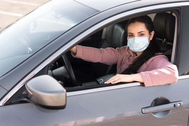 Vrouw in de auto die beschermingsmasker draagt