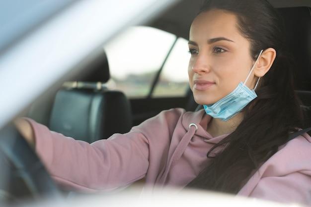 Vrouw in de auto gebruikt het masker niet goed