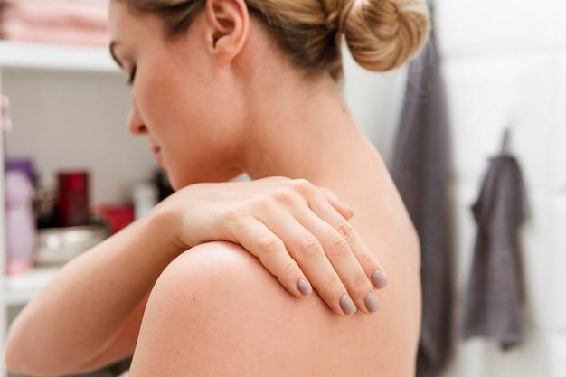 Vrouw in de badkamers met terug hand op haar