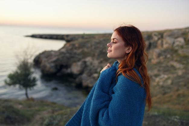 Vrouw in de bergen buiten met een blauwe plaid op haar schouders zijaanzicht