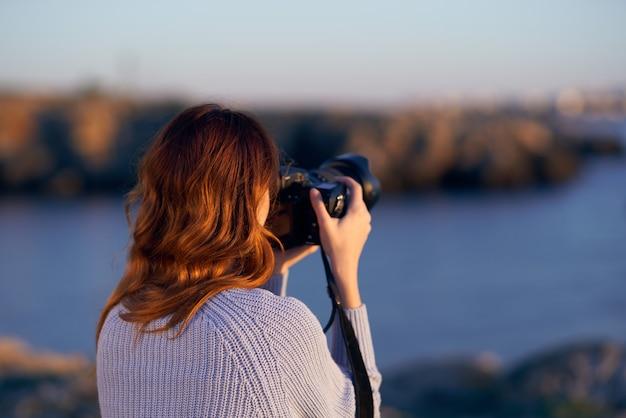 Vrouw in de bergen in de buurt van de zee bij zonsondergang met een professional