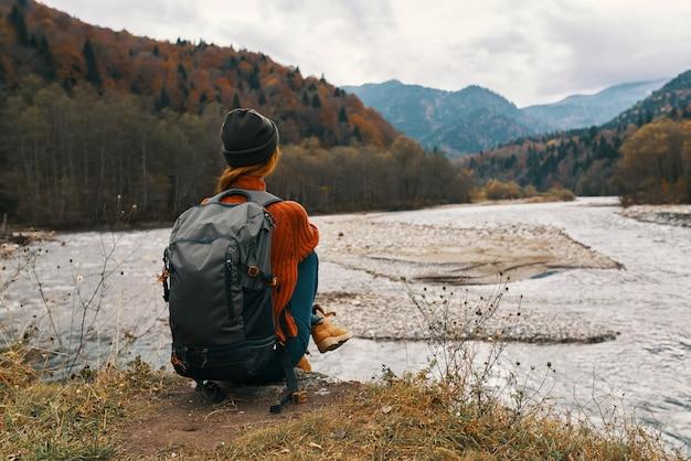 Vrouw in de bergen in de herfst met een rugzak zit aan de oever van de rivier en kijkt naar de hoge