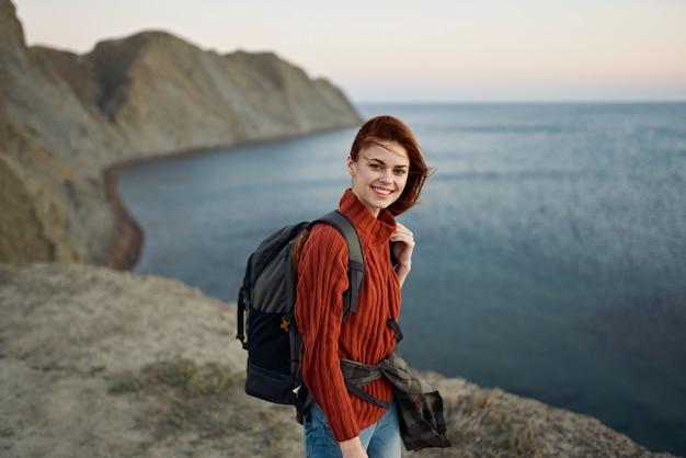 Vrouw in de bergen met een rugzak in de buurt van de zee en hoge rotsen bovenaanzicht