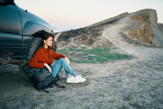 Vrouw in de bergen op het zand met een rugzak in de buurt van het bovenaanzicht van de auto