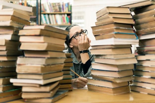 Vrouw in de bibliotheek voor boekenkasten. concept van onderwijs