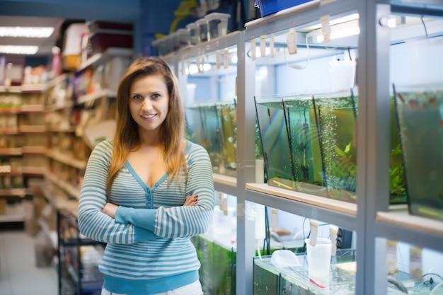 Vrouw in de buurt van aquaria met vissen