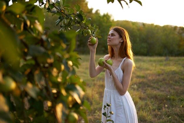 Vrouw in de buurt van bomen met appels in handen op de natuur in de zomer.
