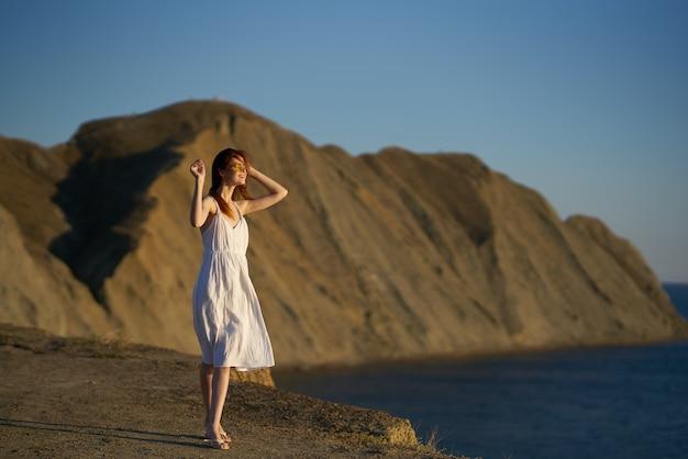 Vrouw in de buurt van de zee in de bergen reizen toerisme avontuur model