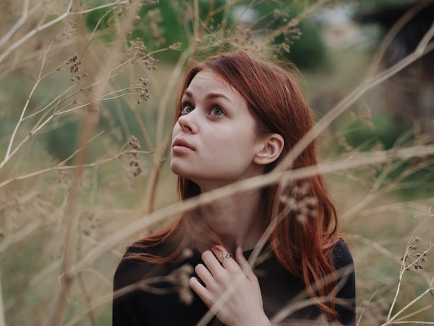 Vrouw in de buurt van droge takken van bomen op de natuur in de herfst in het bos