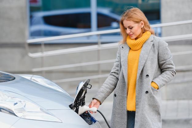 Vrouw in de buurt van een elektrische huurauto. voertuig opgeladen bij het laadstation.