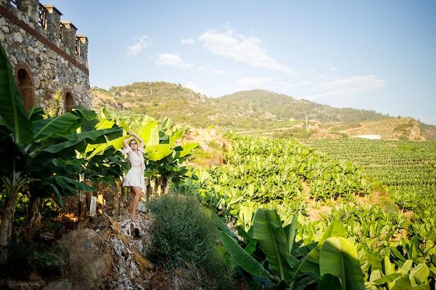 Vrouw in de buurt van een groot groen blad van een bananenboom in de natuur in het park. tropische planten en aantrekkelijk meisje lopen