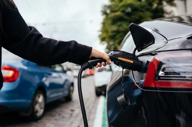 Vrouw in de buurt van elektrische auto. voertuig opgeladen bij het laadstation.