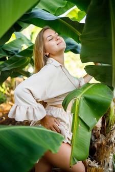 Vrouw in de buurt van groene bladeren van bananenstruiken op de natuur in een park op een tropische plek, ze is in een beige rok en een blouse