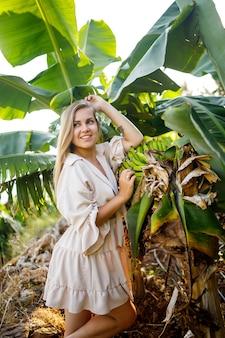 Vrouw in de buurt van groot groen blad van bananenboom op de natuur in het park. tropische planten