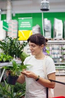 Vrouw in de buurt van planken met bloemen binnen in de winkel