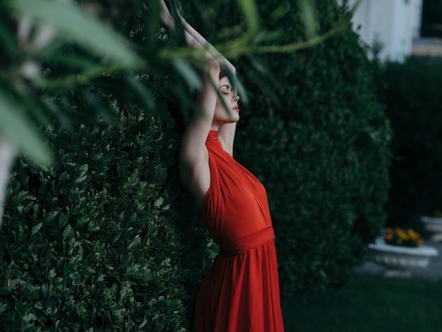 Vrouw in de buurt van struik in rode jurk en sprookjesachtige tuindecoratie