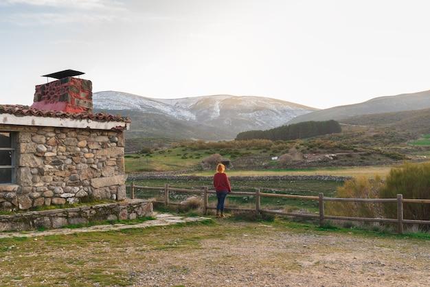 Vrouw in de deuropening van een hut kijkend naar het landschap met bergen op de achtergrond