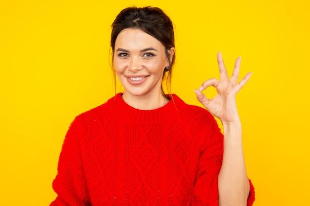 Vrouw in de felgekleurde trui die ok teken toont.