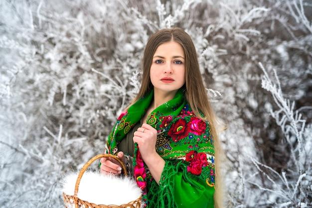 Vrouw in de groene mand van de sjaalholding in de winterpark