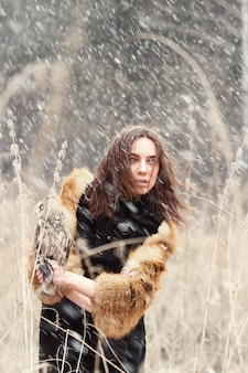 Vrouw in de herfst in bontjas met uil op hand eerste sneeuw. mooie donkerbruine vrouw met lang haar in aard, die een uil houdt. romantische, delicate dameslook