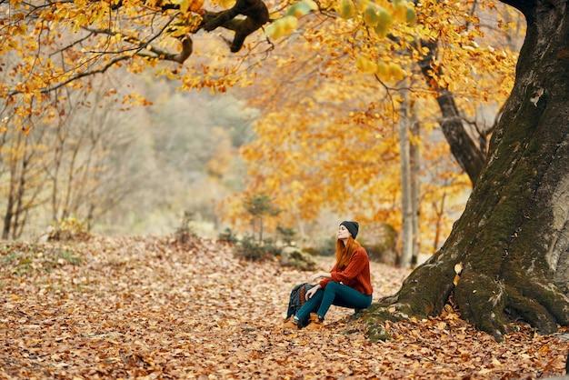 Vrouw in de herfst in het park bij een grote boom en in een rugzak op de grond