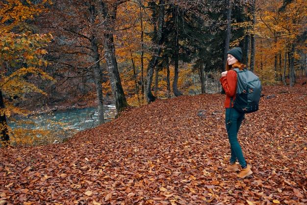Vrouw in de herfst in het park met gevallen bladeren en een rugzak op haar achterste rivier op de achtergrond