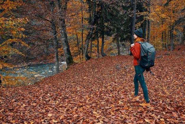 Vrouw in de herfst in het park met gevallen bladeren en een rugzak op haar rug rivier op de achtergrond