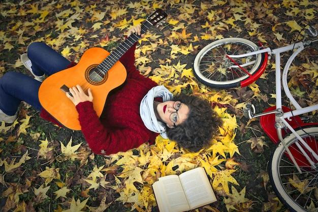 Vrouw in de herfst met een gitaar