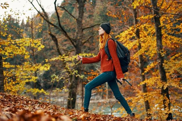 Vrouw in de herfstbos dichtbij het gele bladeren van het rivierlandschapstoerisme