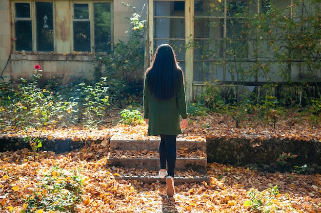 Vrouw in de herfstbos met huis