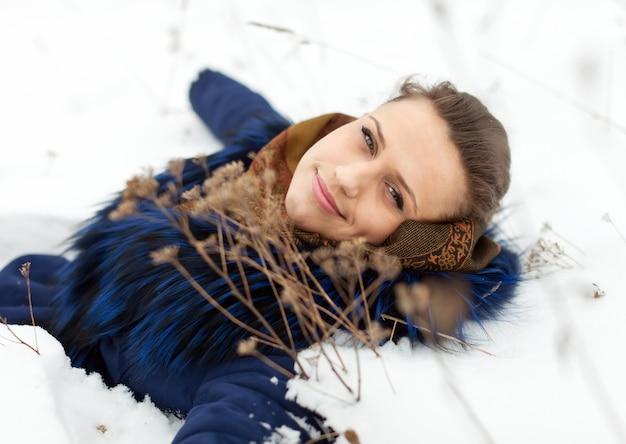 Vrouw in de jas op de sneeuw liggen