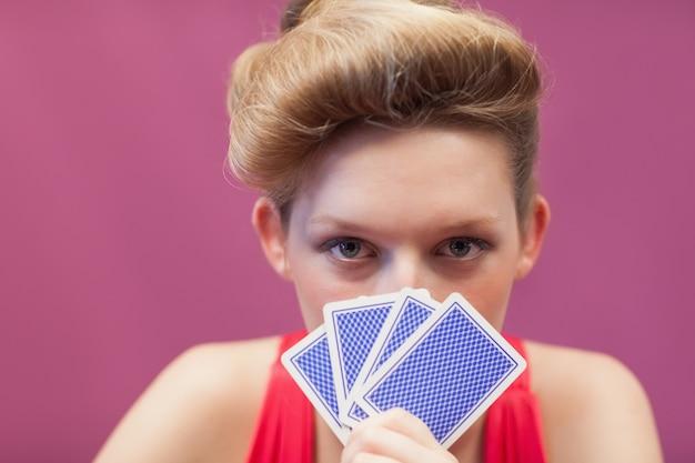 Vrouw in de kaarten van een casinoholding van aangezicht tot aangezicht