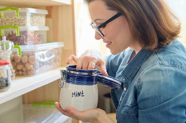 Vrouw in de keuken met blikje droge munt, voedsel opslag, bijkeuken