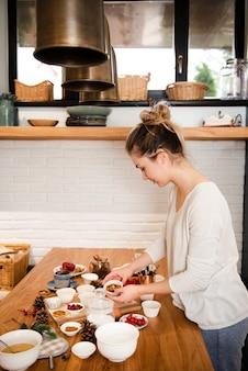 Vrouw in de keuken met cake die ingrediënten verfraait